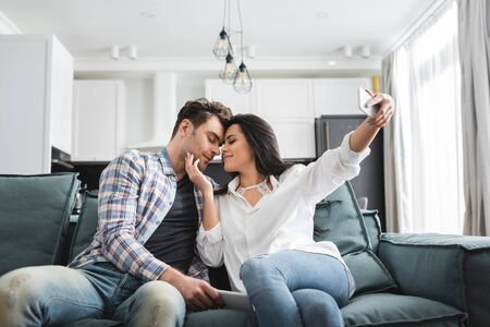 Selective focus of young woman touching boyfriend while taking selfie with smartphone at home