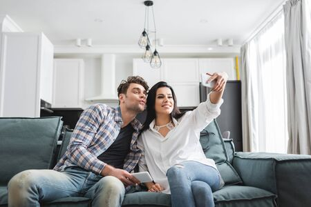 Smiling woman taking selfie with smartphone near boyfriend on couch at home