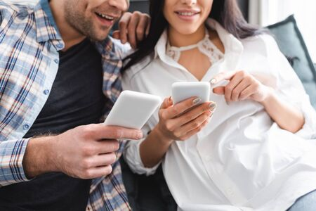 Cropped view of smiling woman pointing with finger at smartphone near boyfriend