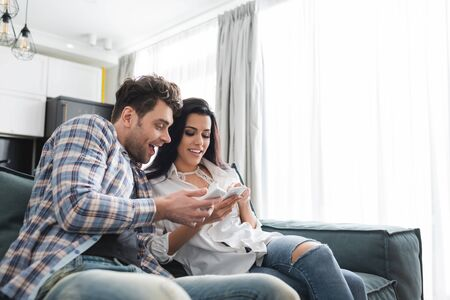 Selective focus of cheerful couple using smartphones on couch in living room Фото со стока