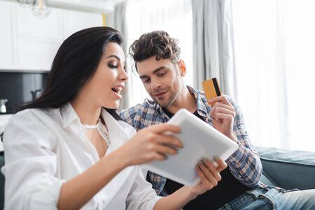 Selective focus of man holding credit card near excited girlfriend showing digital tablet at home Фото со стока