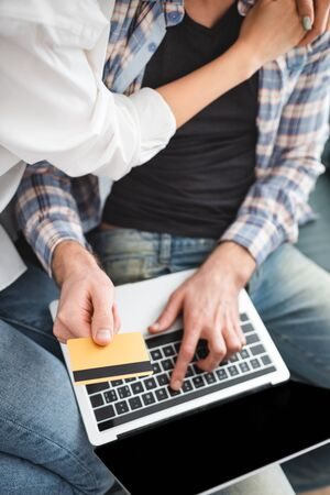 Top view of woman embracing boyfriend using credit card and laptop at home Фото со стока