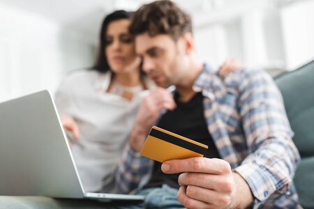 Selective focus of man holding credit card while using laptop near girlfriend at home