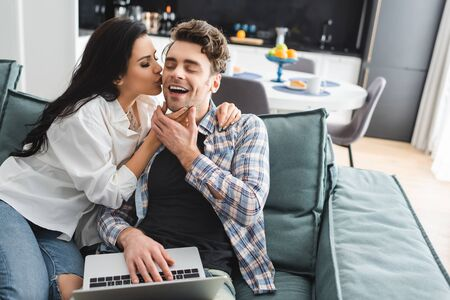 Selective focus of attractive girl kissing cheerful boyfriend using laptop on couch