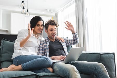 Smiling couple having video call on laptop in living room Фото со стока