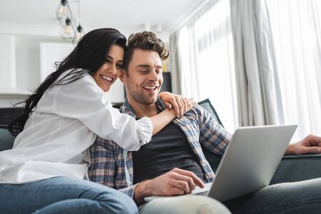 Selective focus of smiling woman embracing boyfriend using laptop at home Zdjęcie Seryjne