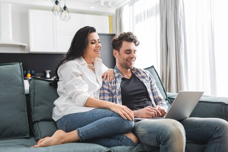 Smiling woman sitting near handsome boyfriend using laptop on couch at home Фото со стока