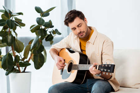 Handsome man playing acoustic guitar on couch