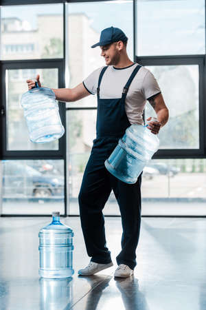 cheerful delivery man in uniform looking at empty bottles near gallon of water Imagens
