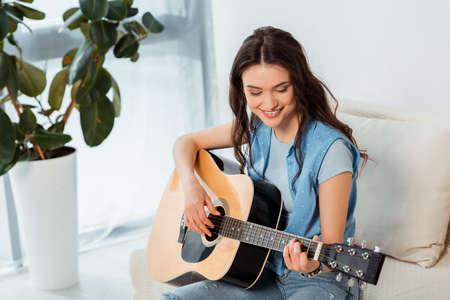 Beautiful smiling woman playing acoustic guitar in living room Stock fotó