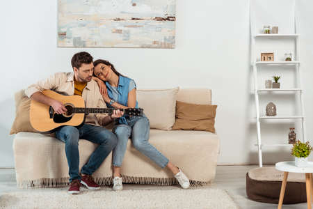 Handsome man playing acoustic guitar near smiling woman on sofa at home