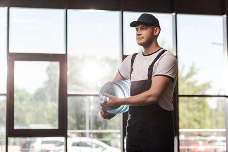 handsome delivery man in uniform and cap holding bottled water