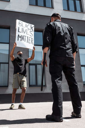 selective focus of african american man with scarf on face holding placard with black lives matter lettering near policeman with baton on street, racism concept