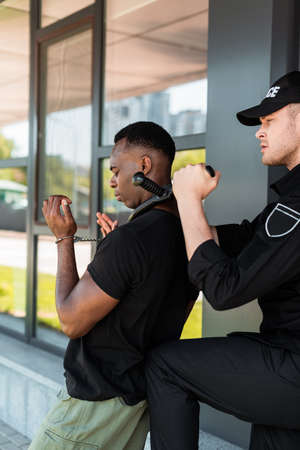 angry policeman in cap holding police baton near throat of handcuffed african american man, racism concept