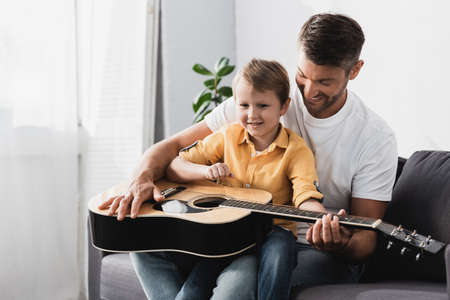 smiling boy sitting of fathers knees and learning how to play acoustic guitar