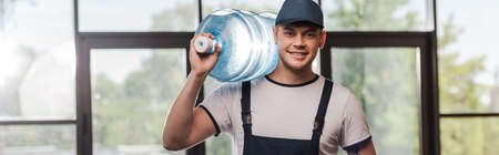 panoramic concept of cheerful delivery man in cap and uniform holding bottled water Imagens