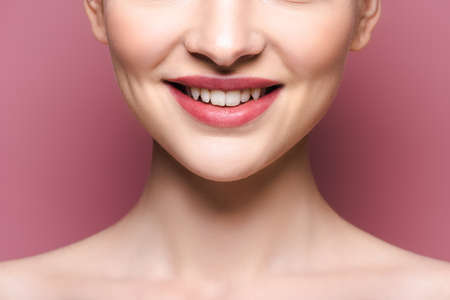 cropped view of happy young woman with lipstick on lips on pink