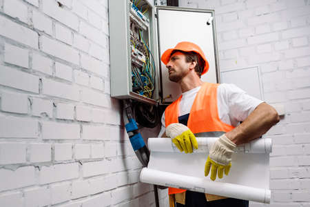 Handsome electrician holding blueprint near electrical distribution box