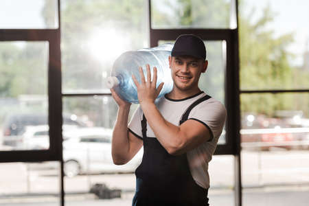 happy delivery man in uniform holding bottled water Imagens
