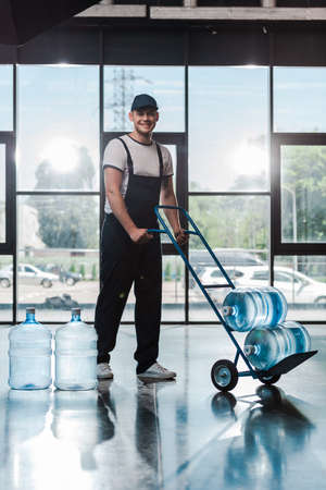 cheerful delivery man in uniform holding hand truck with bottled water Imagens
