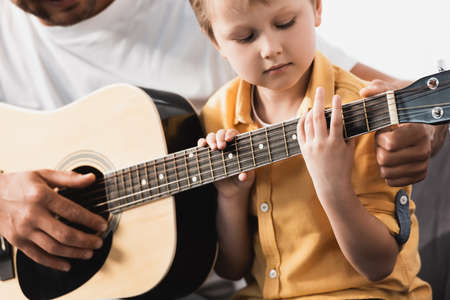 cropped view of father teaching attentive son how to play acoustic guitar