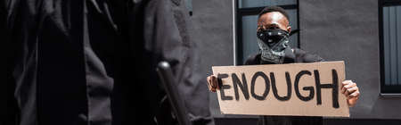 selective focus of african american man with scarf on face holding placard with enough lettering near policeman with baton on street, racism concept