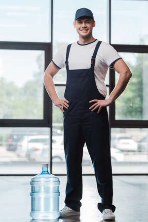 cheerful delivery man in uniform standing with hands on hips near bottled water Imagens