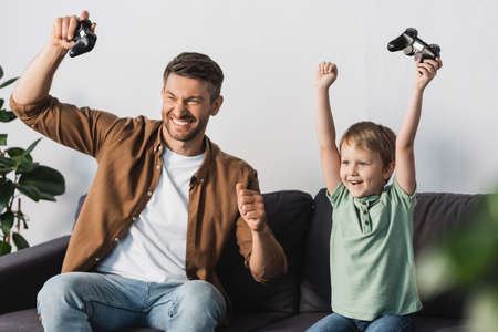 excited father and son showing winner gestures while holding joysticks