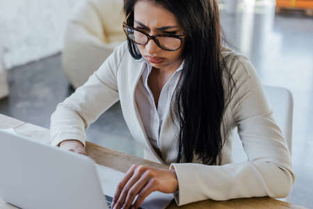 frustrated businesswoman in glasses using laptop near notebook on table 版權商用圖片