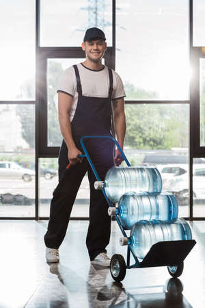 cheerful delivery man in cap and uniform holding hand truck with bottled water