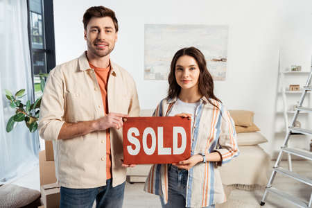 Smiling man holding nameplate with sold lettering near girlfriend in living room