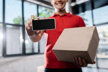 cropped view of happy delivery man holding smartphone with blank screen and carton box