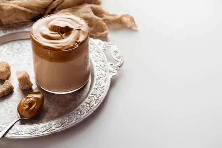 delicious Dalgona coffee in glass near cloth, brown sugar and spoon on silver platter on white background
