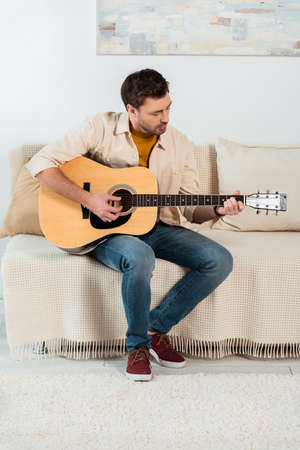 Young man performing on acoustic guitar on sofa in living room Stock fotó