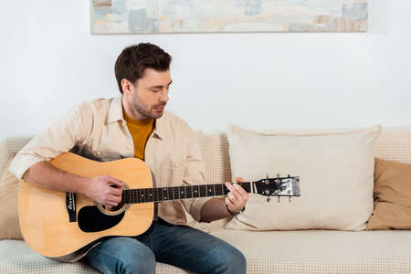 Handsome man playing acoustic guitar on sofa in living room