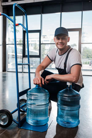 happy delivery man in uniform sitting near hand truck with purified water in bottles