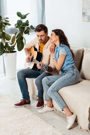 Smiling girl looking at boyfriend playing acoustic guitar at home Stock fotó