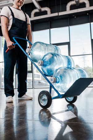 cropped view of cheerful delivery man in uniform holding hand truck with bottled water Imagens