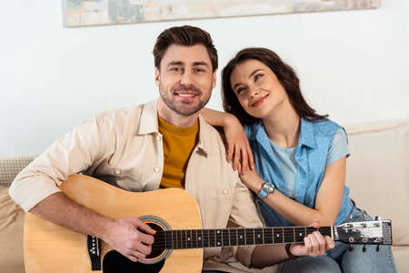 Handsome man smiling at camera while playing acoustic guitar near girlfriend