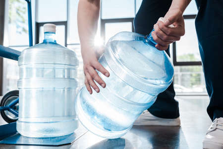 cropped view of delivery man holding blue bottle with water near hand truck Imagens