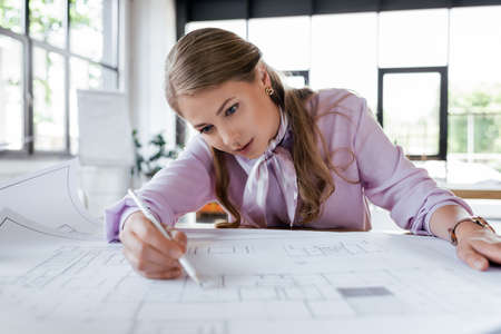 selective focus of attractive businesswoman drawing blueprints in office