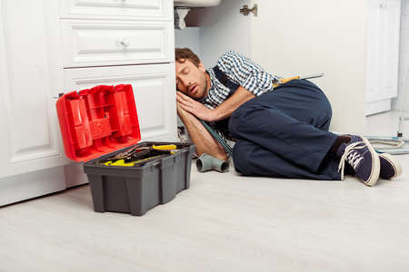 Plumber sleeping on floor near toolbox and sink in kitchen