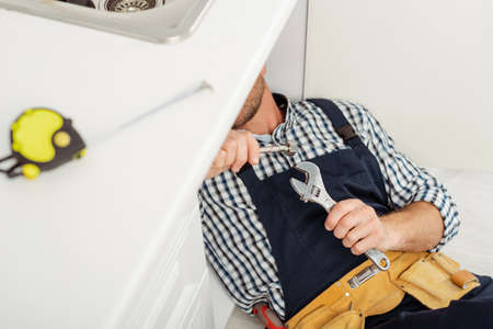 Selective focus of plumber in overalls holding wrench and metal pipe while fixing kitchen sink