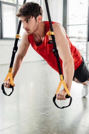 focused and athletic man working out with elastics in gym
