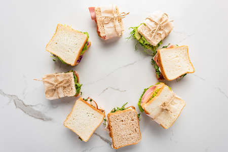 top view of fresh sandwiches arranged in round frame on marble white surface