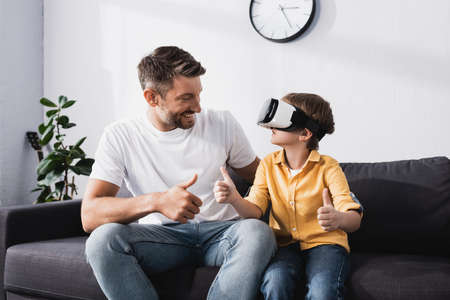 smiling man and son in vr headset showing thumbs up while sitting on sofa