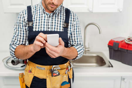 Cropped view of workman in tool belt using smartphone while working in kitchen
