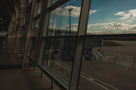 Glass of window with facade of airport building with cloudy sky at background