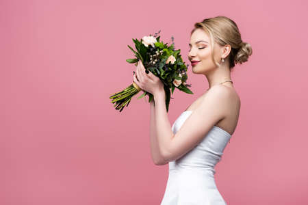 happy bride in white wedding dress smelling flowers isolated on pink
