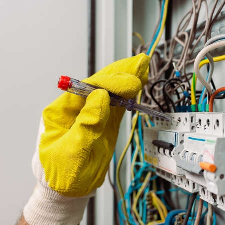Cropped view of electrician in glove using screwdriver while repairing electrical distribution box Banco de Imagens